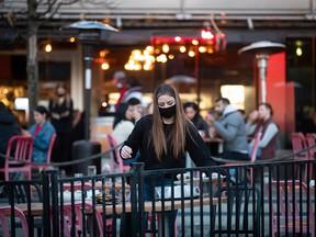 Een gemaskerde bediende veegt op 2 april 2021 een tafel af op een terras van een restaurant in Vancouver.
